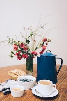 Biscoito; amoras; geleia e xícara de café na mesa de madeira contra o fundo branco