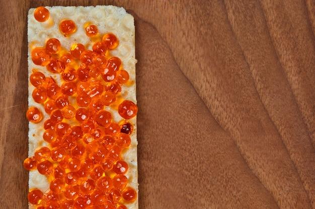 Biscoito com caviar vermelho na madeira.