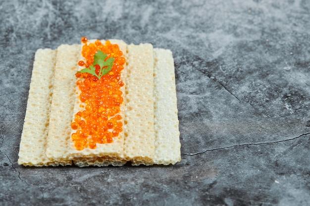 Biscoito com caviar vermelho.