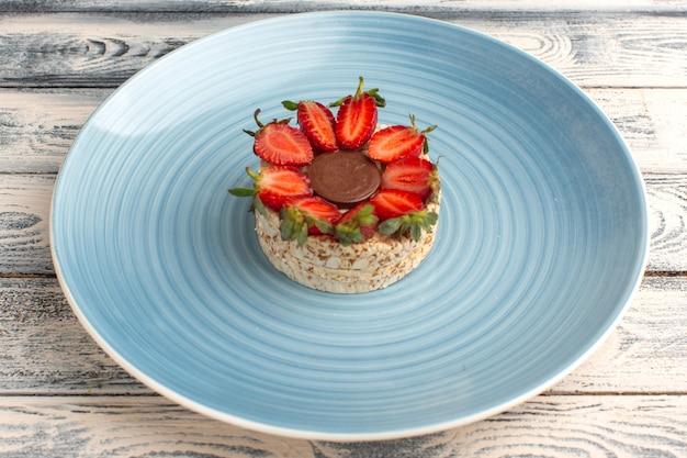Biscoito com morangos e chocolate redondo dentro de prato azul em cinza rústico
