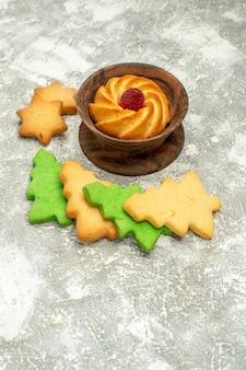 Biscoito de biscoitos de árvore de natal em uma tigela na superfície cinza do espaço livre