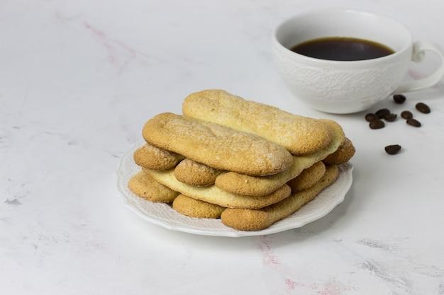 Biscoito de biscoitos savoyardi e café em uma superfície de mármore branco