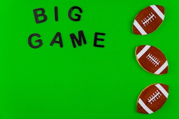Biscoito de bola de rugby com grande jogo de texto sobre fundo verde. fundo de futebol americano.
