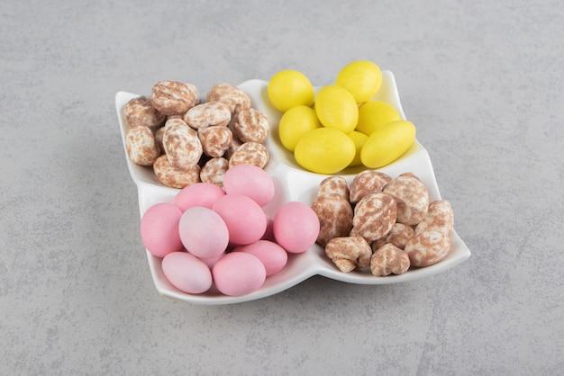 Biscoito de canela e gomas no prato, na superfície de mármore