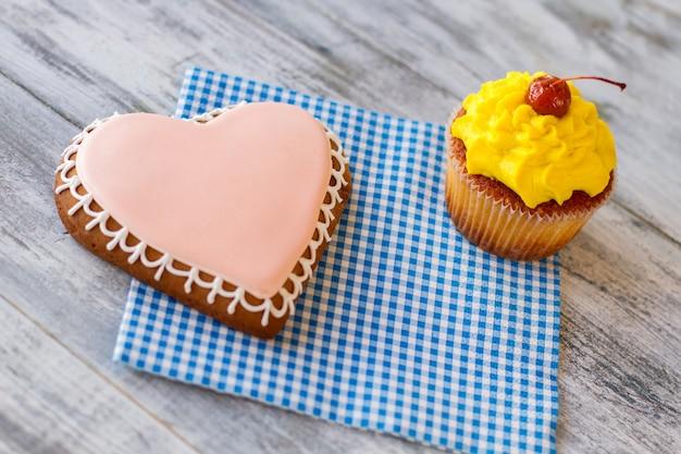 Biscoito de coração e bolinho de bolinho amarelo em guardanapo azul são um sinal de atenção para a amada ...