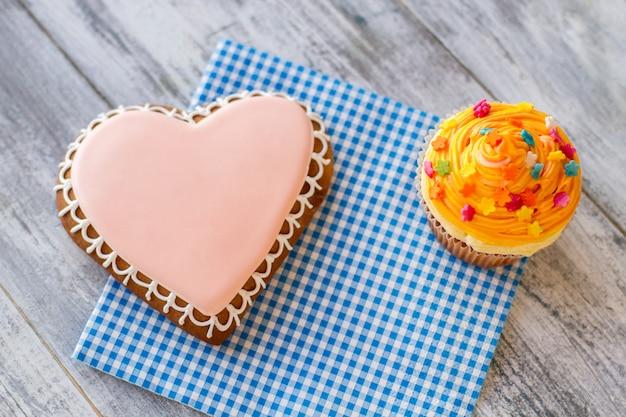 Biscoito de coração e vista superior de cupcake de laranja de sobremesas de confeitaria na mesa de madeira cinza feriado para ...