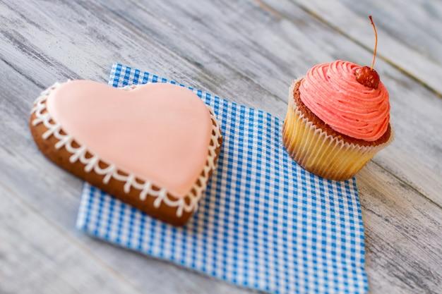Biscoito de coração rosa e confeitaria de cupcake em guardanapo xadrez saborosa sobremesa para dois vamos comemorar ...