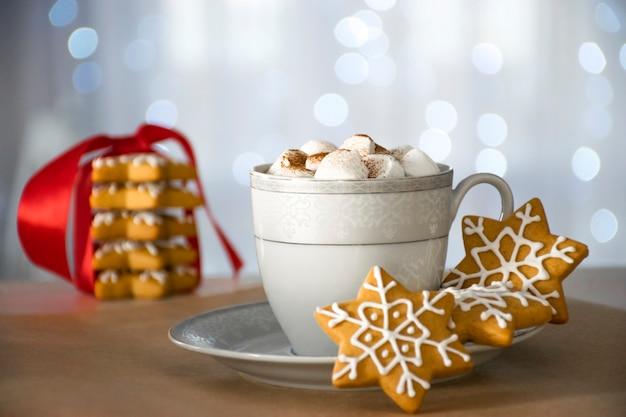 Biscoito de gengibre artesanal de natal tradicional e copo de bebida quente de inverno com marshmallow, pilha de biscoito e bokeh no fundo.