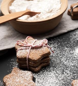 Biscoito de gengibre assado em forma de estrela polvilhado com açúcar de confeiteiro sobre uma mesa preta e ingredientes, close up