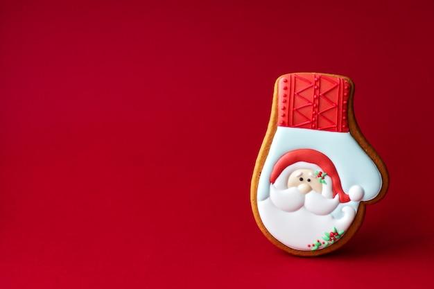 Biscoito de gengibre da luva de inverno com retrato de papai noel no vermelho