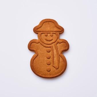 Biscoito de gengibre de ano novo ou em forma de boneco de neve, isolado no fundo branco. imagem quadrada. vista do topo.