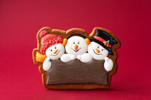 Biscoito de gengibre de boneco de neve bonito no vermelho