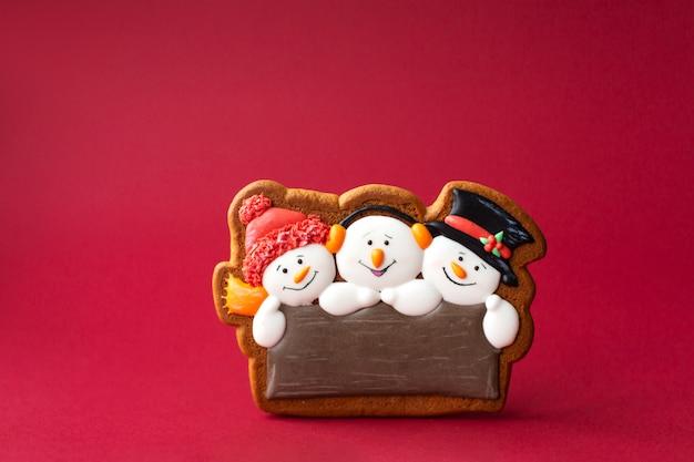 Biscoito de gengibre de boneco de neve bonito sobre fundo vermelho.
