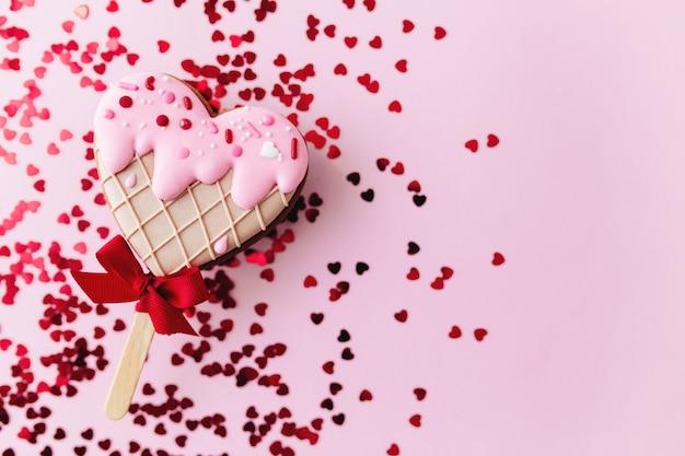 Biscoito de gengibre de coração de sorvete derretendo. namorados. fundo rosa, glitter. foto de alta qualidade