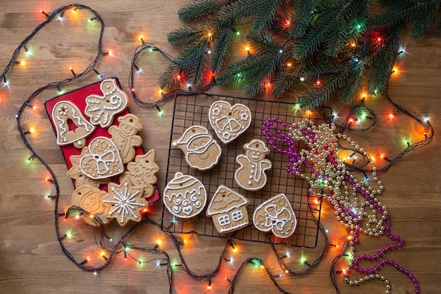 Biscoito de gengibre de natal na mesa de madeira com galhos de pinheiro e guirlanda