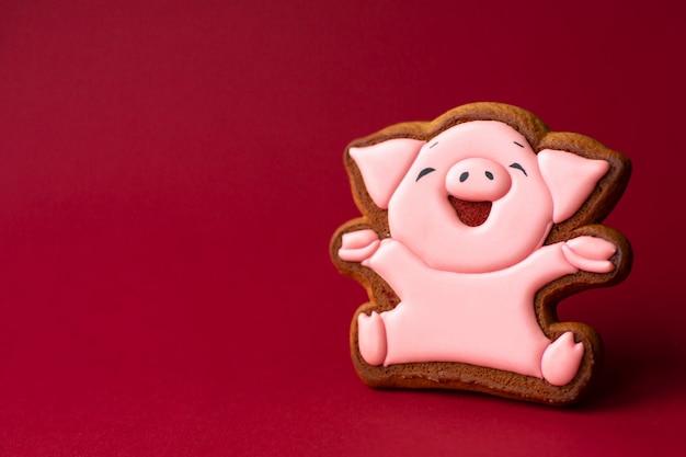 Biscoito de gengibre de porco rosa bonito sobre fundo vermelho. comida tradicional de natal. conceito de férias de natal e ano novo. copyspace