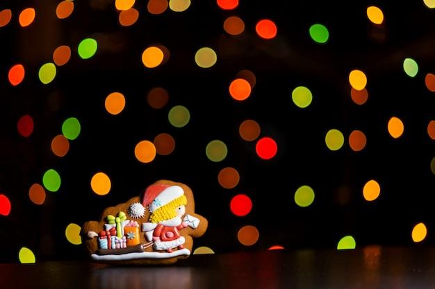 Biscoito de gengibre do carteiro papai noel sobre luzes coloridas desfocadas da guirlanda