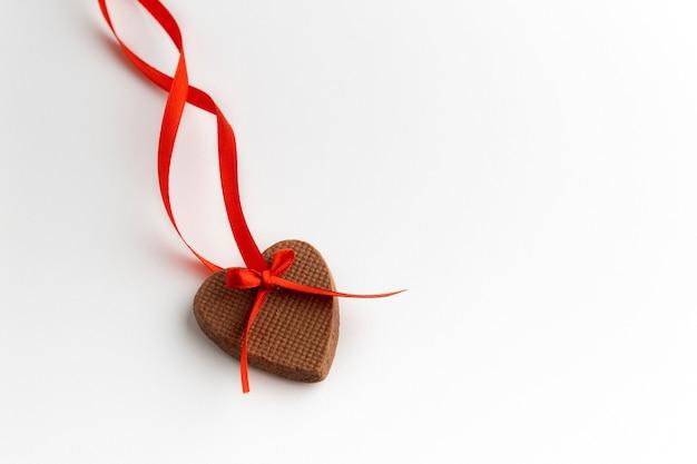 Biscoito de gengibre em forma de coração com fita vermelha sobre fundo branco. dia dos namorados.