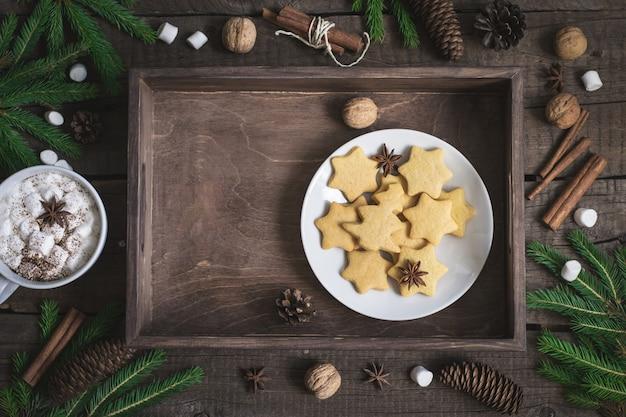 Biscoito de gengibre em forma de estrelas na bandeja rústica. fundo de comida de natal.