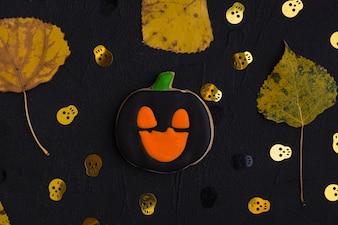 Biscoito de Halloween, folhas secas e crânios ornamentais