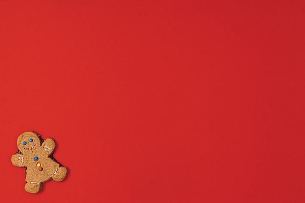 Biscoito de homem-biscoito de natal com glacê, açúcar granulado sobre um fundo vermelho de mesa. plano de papel de parede de ano novo lay. padrão de férias com espaço de cópia.