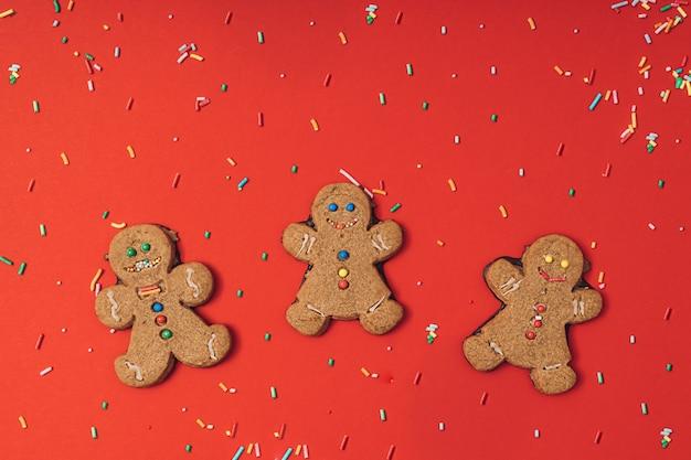 Biscoito de homem-biscoito de natal com glacê, açúcar granulado sobre um fundo vermelho de mesa. plano de papel de parede de ano novo lay. padrão de férias.