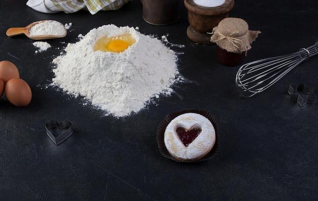 Biscoito de pastelaria com um coração vermelho jam e açúcar em pó de confeiteiro