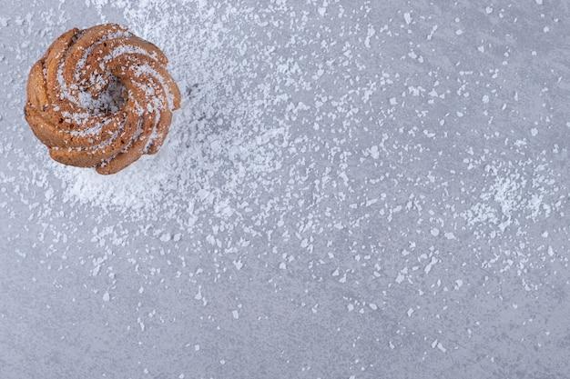 Biscoito delicioso em uma pilha de pó de baunilha na superfície de mármore Foto gratuita
