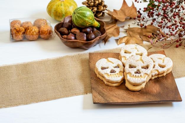 Biscoito doce de caveira na placa de madeira, castanhas e abóboras em cima da mesa, preparada para o halloween.