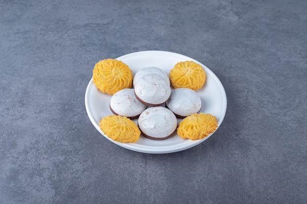 Biscoito e bolos pop em um prato na mesa de mármore.