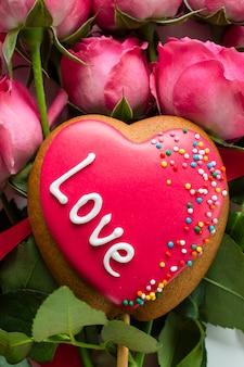 Biscoito em forma de coração no buquê de rosas