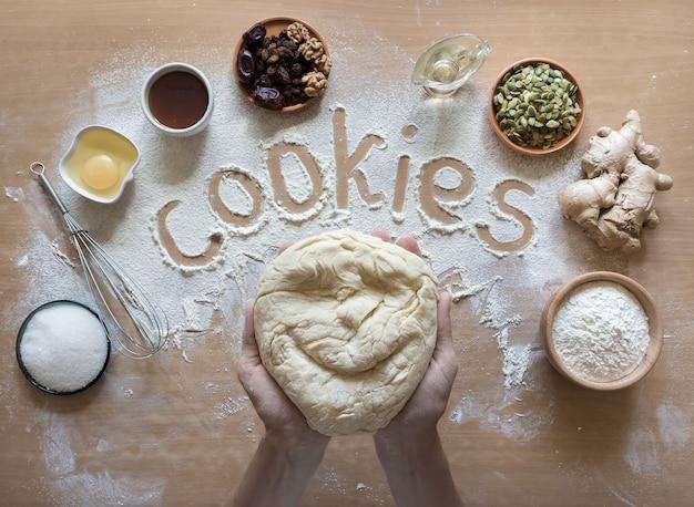 Biscoito, escrito na farinha e vista superior do conjunto de produtos para cozinhar biscoitos no halloween. modelagem de tortas pequenas com massa de repolho.