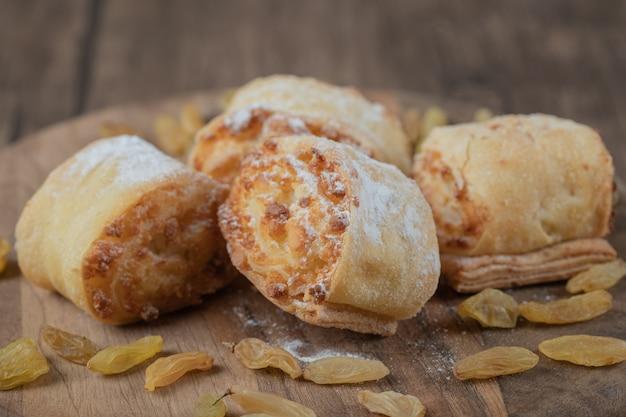 Biscoito frito rola com passas e recheios doces.