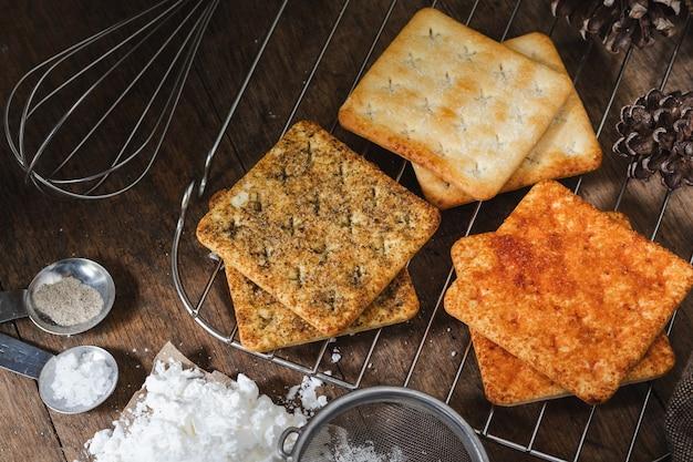 Biscoito quadrado de biscoitos secos em uma mesa de madeira textura de madeira fundo escuro biscoitos secos
