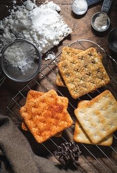 Biscoito quadrado de bolachas secas em uma mesa de madeira com fundo escuro de textura de madeira