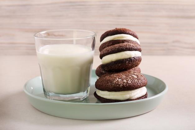 Biscoito recheado de chocolate com recheio de natas, servido com copo de leite