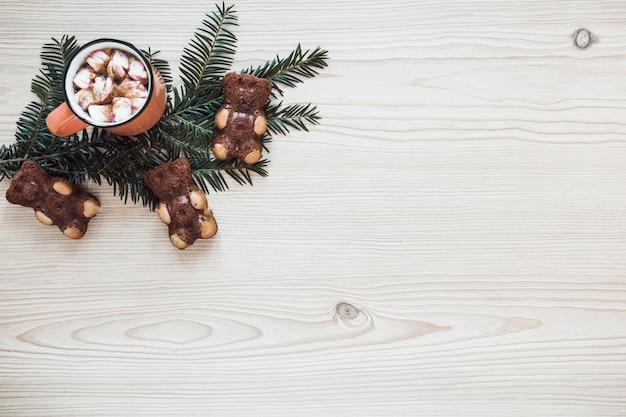 Biscoito ursos perto de ramo de coníferas e chocolate quente
