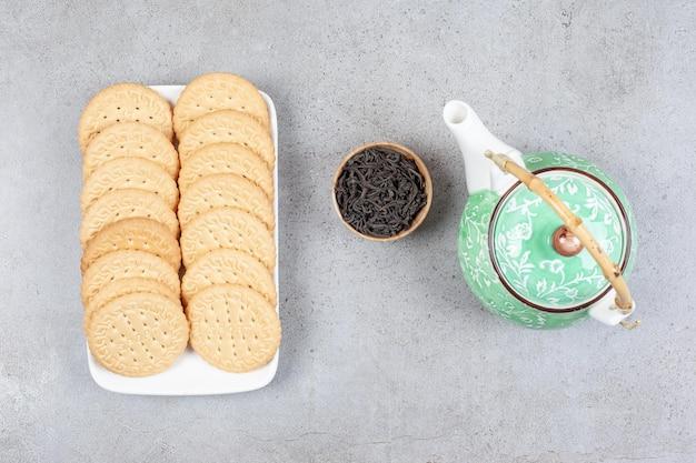 Biscoitos alinhados em uma travessa com um bule e uma pequena tigela de folhas de chá na superfície de mármore