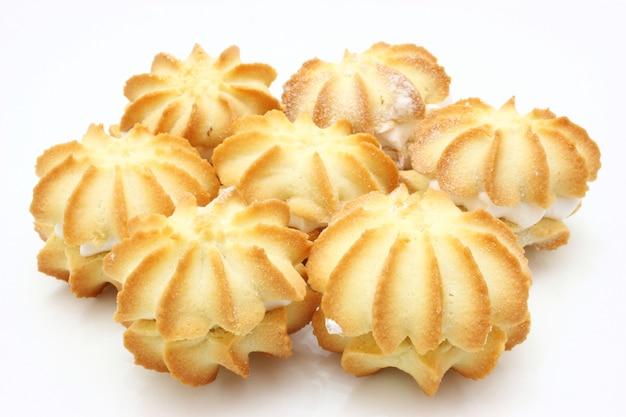 Biscoitos amarelos com recheio branco estão na forma de um círculo