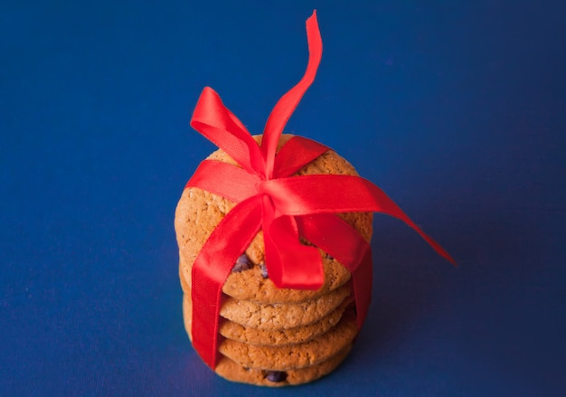 Biscoitos amarrados com uma fita vermelha para um presente no fundo azul
