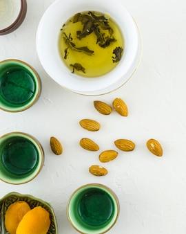 Biscoitos; amêndoas com chá de ervas e xícaras no fundo texturizado branco