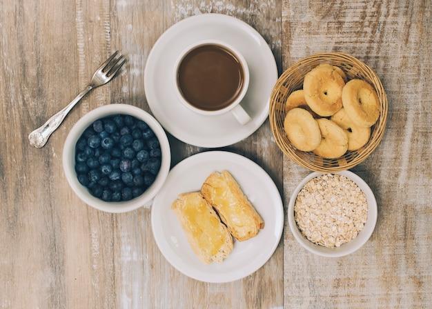 Biscoitos; amoras; aveia; biscoitos e café em pano de fundo de madeira