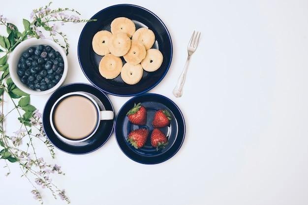 Biscoitos; amoras; café e morangos no pano de fundo branco