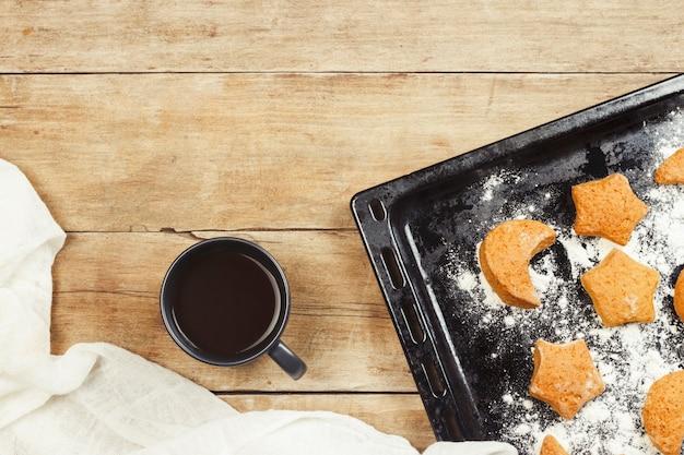 Biscoitos artesanais em uma assadeira e um copo com chá quente ou café numa superfície de madeira. o conceito de habilidades culinárias caseiras. vista plana leiga, superior.