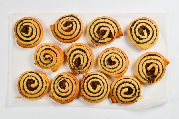 Biscoitos assados com passas e sementes de papoula, isoladas no fundo branco.