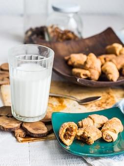 Biscoitos bagels de massa recheada com leite condensado em prato de madeira, copo de leite