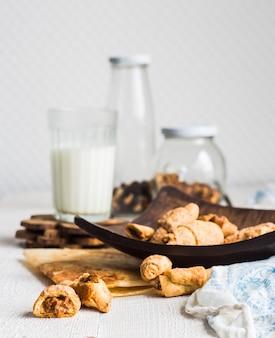 Biscoitos bagels de pastel recheado com leite condensado em prato de madeira, copo de leite, sobremesa em branco