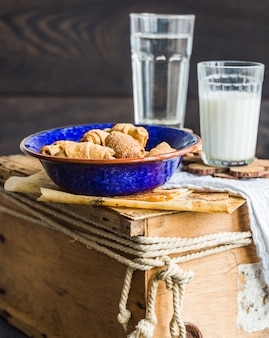 Biscoitos bagels de uma pastelaria curta com recheio, leite, no prato azul, pastéis doces em uma madeira