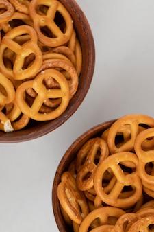 Biscoitos bretzels com sal em tigelas de madeira isoladas em uma superfície branca