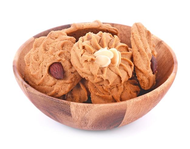 Biscoitos, café de amêndoa em tigela de madeira com fundo branco